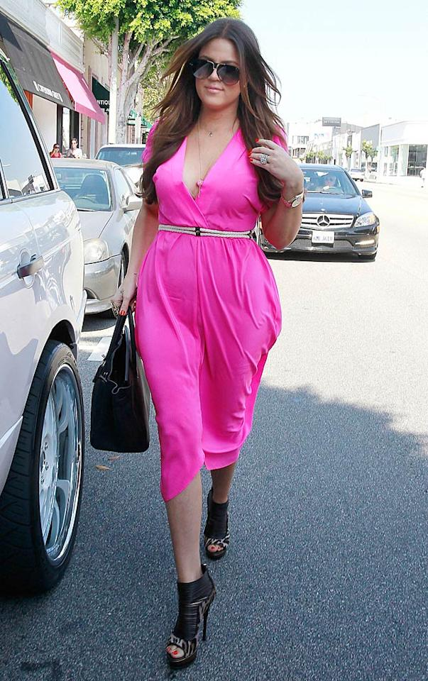 "About an hour later, Kourtney's younger sister Khloe was photographed exiting the designer's boutique (after trying on her bridesmaid dress) in an equally atrocious outfit. I find both items incredibly unflattering, but what do you make of her belted, bubblegum-pink jumpsuit and leopard print peep-toes? Bruja, Juan Sharma/<a href=""http://www.pacificcoastnews.com/"" target=""new"">PacificCoastNews.com</a> - August 10, 2011"