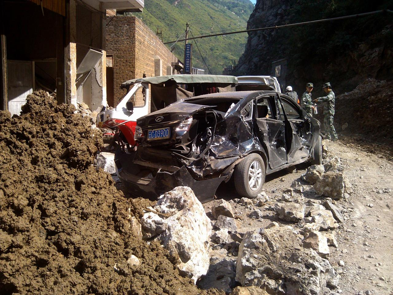 In this photo provided by China's Xinhua News Agency, damaged cars are seen in Luozehe town, Yiliang County, southwest China's Yunnan Province, Friday, Sept. 7, 2012. A series of earthquakes collapsed houses and triggered landslides in a remote mountainous part of southwestern China on Friday, killing dozens of people with the toll expected to rise. Damage was preventing rescuers from reaching some outlying areas, and communications were disrupted. (AP Photo/Xinhua, Zhou Hongpeng)