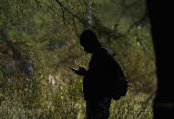 A migrant checks his cellphone at an improvised refugee camp at a sport park in Ciudad Acuña, Mexico, Wednesday, Sept. 22, 2021. (AP Photo/Fernando Llano)