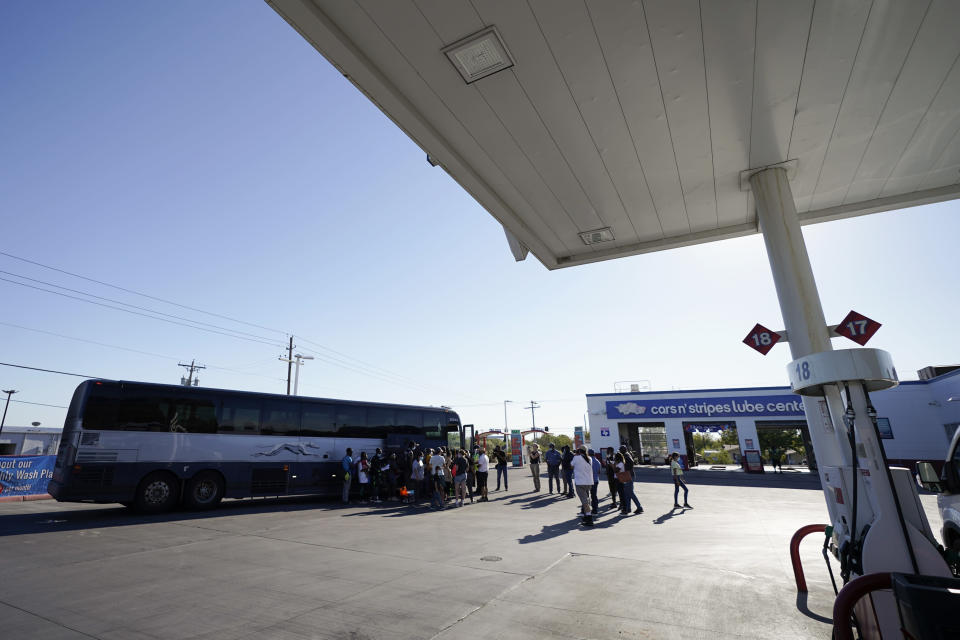 A bus picks up travelers, mostly migrants from Haiti released from A U.S. Customs and Border Protection custody, at a gas station that serves as a bus terminal, Thursday, Sept. 23, 2021, in Del Rio, Texas. Migrants released are greeted by a humanitarian organization, which facilitates bus tickets to San Antonio as they continue their journey. (AP Photo/Julio Cortez)