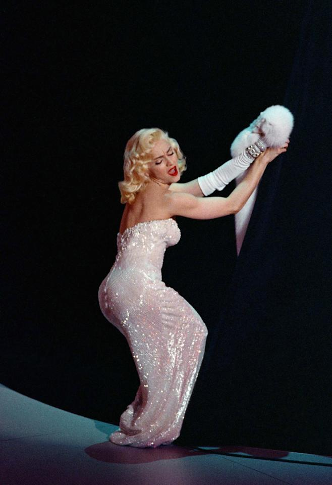 "FILE - In this March 25, 1991 file photo, Madonna performs ""Sooner or Later (I Always Get My Man)"" from the film ""Dick Tracy"" during the 63rd Annual Academy Awards show at the Shrine Auditorium, in Los Angeles. The song won an Oscar for best song. Madonna has famously appropriated Marilyn Monroe's look into her image. Monroe passed away a half-century ago this week, a murky death that remains one of Hollywood's most tantalizing mysteries. But look around: Her legend lives on, more vibrantly than ever. In a twist she surely would have appreciated, this 1950's bombshell has become a 21st-century pop culture phenom. (AP Photo/Reed Saxon, File)"