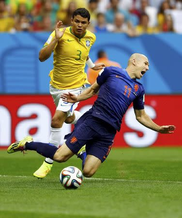 Brazil's Thiago Silva (L) fouls Arjen Robben of the Netherlands to concede a penalty during their 2014 World Cup third-place playoff at the Brasilia national stadium in Brasilia July 12, 2014. REUTERS/Dominic Ebenbichler