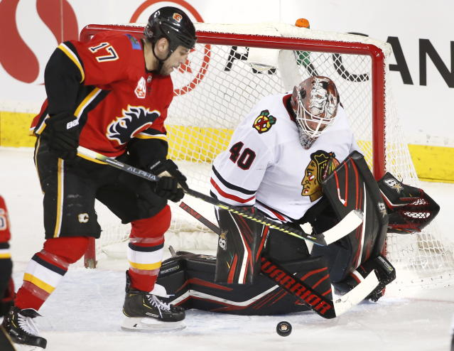 Chicago Blackhawks goaltender Robin Lehner (40) makes a save against Calgary Flames left wing Milan Lucic (17) during the second period of an NHL hockey game Saturday, Feb. 15, 2020, in Calgary, Alberta. (Larry MacDougal/The Canadian Press via AP)