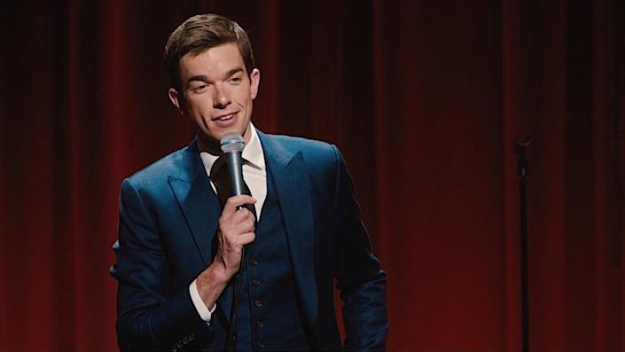 John Mulaney performing a stand-up in a blue suit
