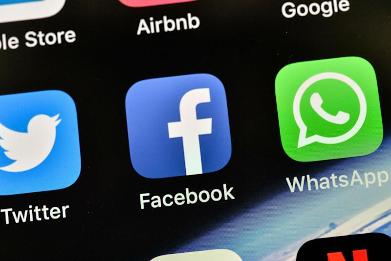 FILE - In this Nov. 15, 2018, file photo the icons of Facebook and WhatsApp are pictured on an iPhone in Gelsenkirchen, Germany. Facebook is already the leader in enabling you to share photos, videos and links. It now wants to be a force in messaging, commerce, payments and just about everything else you do online. (AP Photo/Martin Meissner, File)