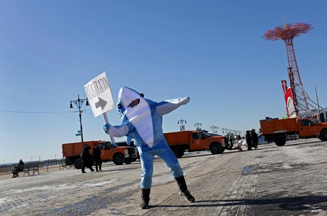 <p>A person in a shark costume directs Polar Bear Club swimmers before their annual icy plunge into the Atlantic Ocean on New Year's Day, January 1, 2018, at Coney Island in the Brooklyn borough of New York City. (Photo: Yana Paskova/Getty Images) </p>