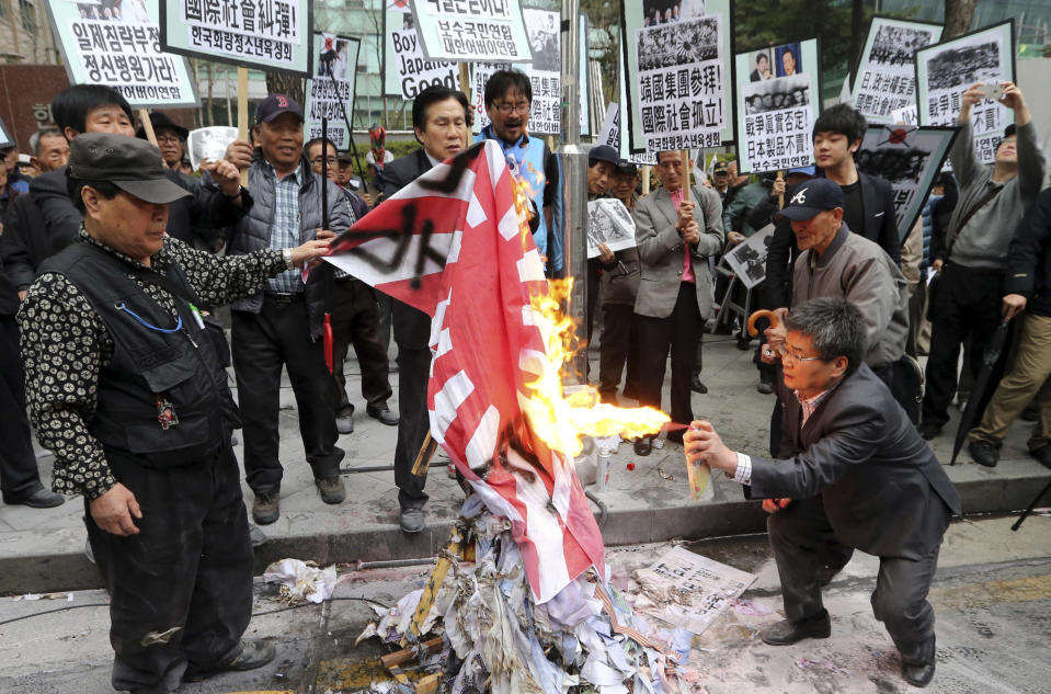 """FILE - In this April 25, 2013, file photo, members from conservative civic organizations burn a Japanese rising sun flag during a rally to protest Japanese lawmakers who made a visit to Yasukuni Shrine in Tokyo, in front of Japanese Embassy in Seoul, South Korea. Japan's """"rising sun"""" flag is raising anger at the Olympics, with some of the host nation's neighbors calling for it to be banned during the Tokyo Games, which start Friday, July 23, 2021. (Lee Jung-hoon/Yonhap via AP, File)"""