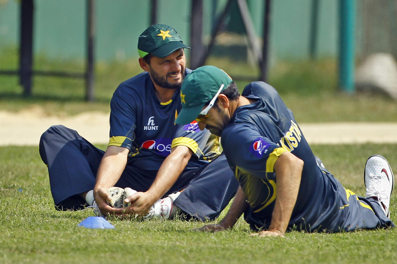 Pakistan's Shahid Afridi, left, and Ahmed Umar Gul stretch during a team practice session in Dhaka, Bangladesh, Friday, March 7, 2014. Pakistan will face Sri Lanka in the Asia Cup final match on Saturday. (AP Photo/A.M. Ahad)