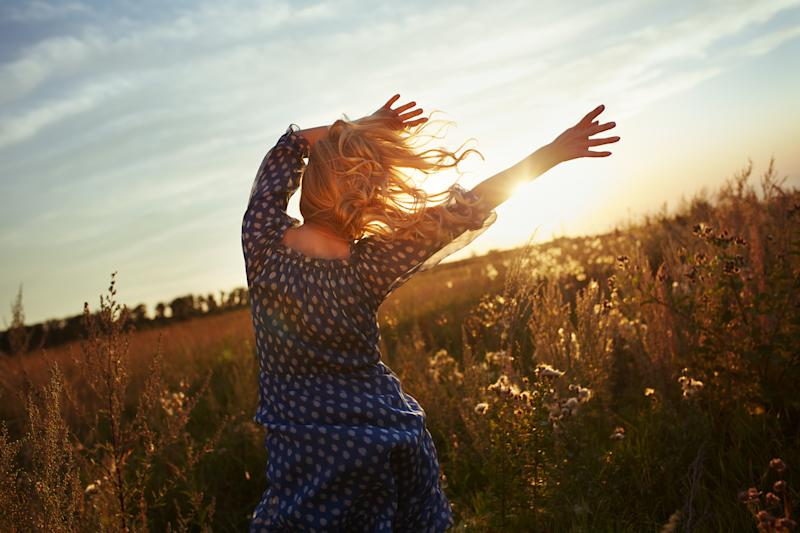 Woman with wavy hair dancing in the meadow during sunset