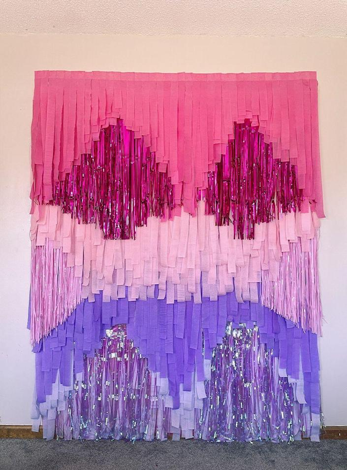 """<p>Whether you're looking for the perfect snack table backdrop or a stunning photo wall, you just need some crepe paper streamers, foil fridge curtains, and a tablecloth. </p><p><strong><em><a href=""""https://prettycolorfullife.com/index.php/2021/03/26/ombre-diy-streamer-backdrop-how-to-make-a-streamer-backdrop-with-balloons/"""" rel=""""nofollow noopener"""" target=""""_blank"""" data-ylk=""""slk:Get the tutorial at Pretty Colorful Life"""" class=""""link rapid-noclick-resp"""">Get the tutorial at Pretty Colorful Life</a>. </em></strong></p><p><a class=""""link rapid-noclick-resp"""" href=""""https://www.amazon.com/Party-Dimensions-Rectangle-Tablecover-108-Inch/dp/B00IMITRHY?tag=syn-yahoo-20&ascsubtag=%5Bartid%7C10070.g.37055923%5Bsrc%7Cyahoo-us"""" rel=""""nofollow noopener"""" target=""""_blank"""" data-ylk=""""slk:SHOP PLASTIC TABLECLOTH"""">SHOP PLASTIC TABLECLOTH</a></p>"""