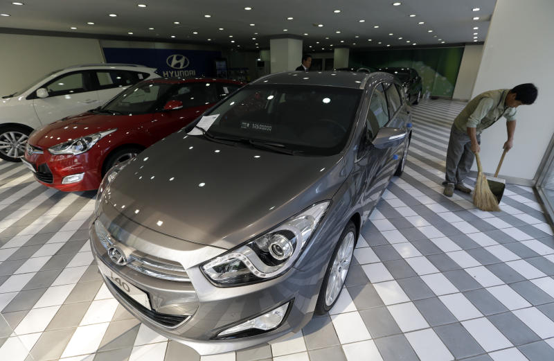 A man sweeps the floor of a Hyundai Motor's showroom in Seoul, South Korea, Thursday, Oct. 25, 2012. Hyundai Motor Co. suffered a fall in third quarter profit versus the previous quarter after strikes dented vehicle production. (AP Photo/Lee Jin-man)