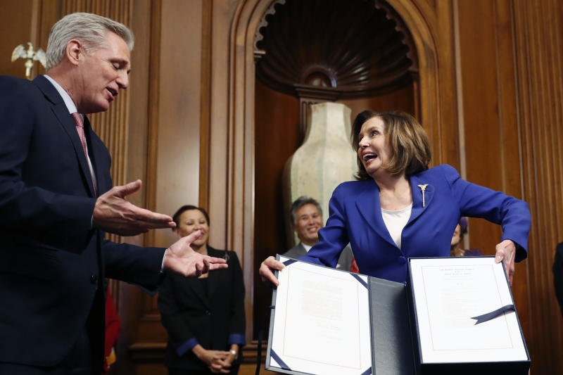 House Speaker Nancy Pelosi of Calif., accompanied by House Minority Leader Kevin McCarthy of Calif., and other legislators, participate in a bill enrollment ceremony for the Coronavirus Aid, Relief, and Economic Security (CARES) Act, after it passed in the House, on Capitol Hill, Friday, March 27, 2020 in Washington. The $2.2 trillion package will head to Trump's desk for his signature. (AP Photo/Andrew Harnik)