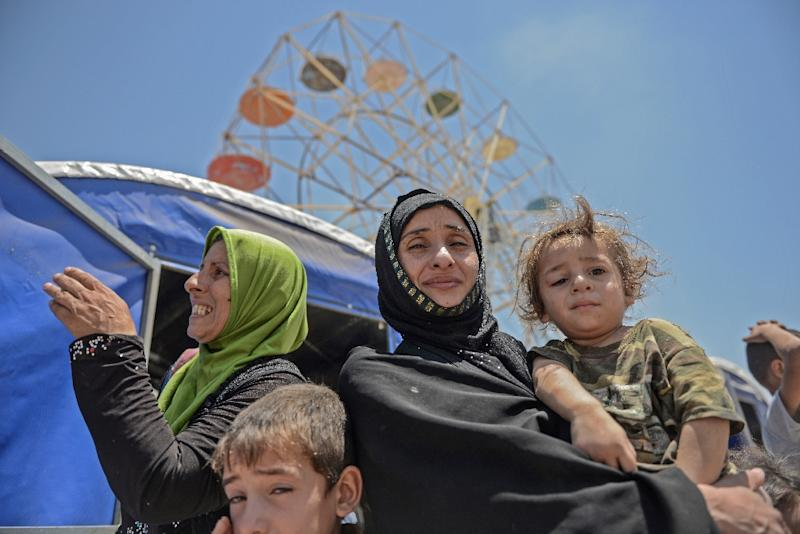 A displaced Iraqi family pose at a temporary camp in the compound of a hotel in Mosul on June 16, 2017