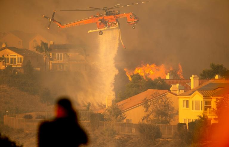 A helicopter drops water to help fight flames as the Saddleridge Fire in the Porter Ranch section of Los Angeles, California on October 11, 2019 (AFP Photo/Josh Edelson)