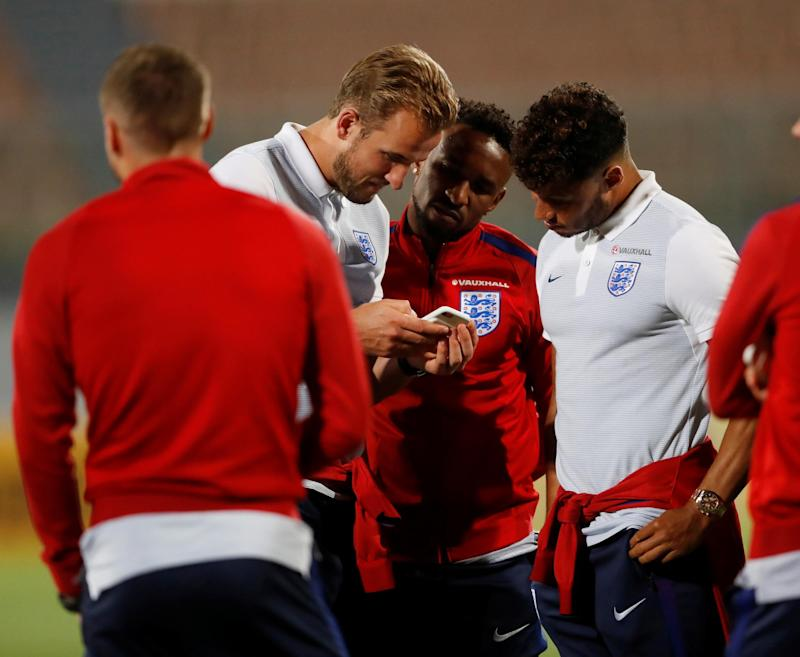 England's Alex Oxlade-Chamberlain, Harry Kane and Jermain Defoe look at a mobile phone during the stadium visit: Reuters/Carl Recine