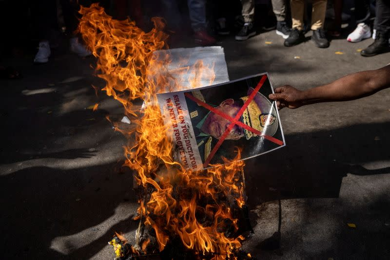 A Myanmar citizen living in India burns a poster of Myanmar's army chief Senior General Min Aung Hlaing with his face crossed out during a protest against the military coup in Myanmar, in New Delhi