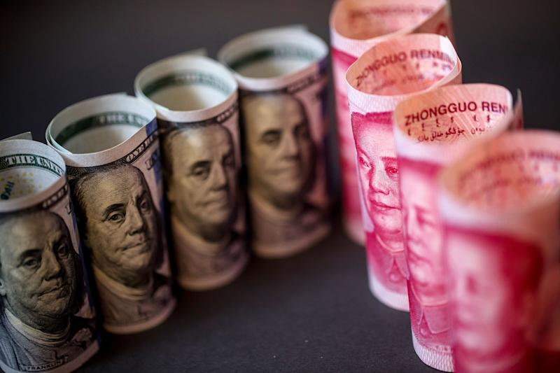 U.S. one-hundred dollar banknotes and Chinese one-hundred yuan banknotes are arranged for a photograph in Hong Kong, China, on Monday, April 15, 2019. China's holdings of Treasury securities rose for a third month as the Asian nation took on more U.S. government debt amid the trade war between the worlds two biggest economies. Photographer: Paul Yeung/Bloomberg via Getty Images