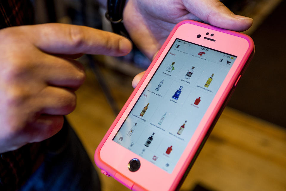 PORTLAND, ME - APRIL 14: Kevin Casey, manager of Old Port Spirits & Cigars, demonstrates the app Drizly that his store is partnering with to deliver liquor in the Portland area starting Thursday, April 14, 2016. (Photo by Gabe Souza/Portland Portland Press Herald via Getty Images)