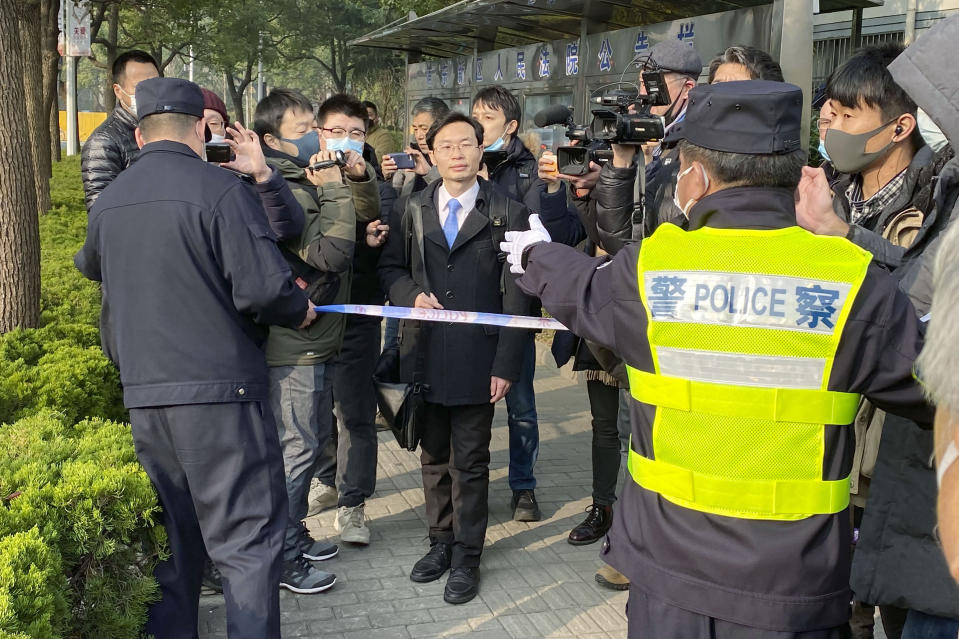 "A police officer tries to stop media as a lawyer, center, of Zhang Zhan arrives at a court in Shanghai, China Monday, Dec. 28, 2020. The Pudong New Area People's Court sentenced Zhang, a former lawyer who reported on the early stage of the coronavirus outbreak to four years in prison on charges of ""picking fights and provoking trouble,"" one of her lawyers said. (Kyodo News via AP)"