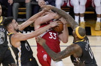 Toronto Raptors center Marc Gasol (33) is defended by Golden State Warriors guard Klay Thompson, left, and center DeMarcus Cousins during the second half of Game 4 of basketball's NBA Finals in Oakland, Calif., Friday, June 7, 2019. (AP Photo/Tony Avelar)