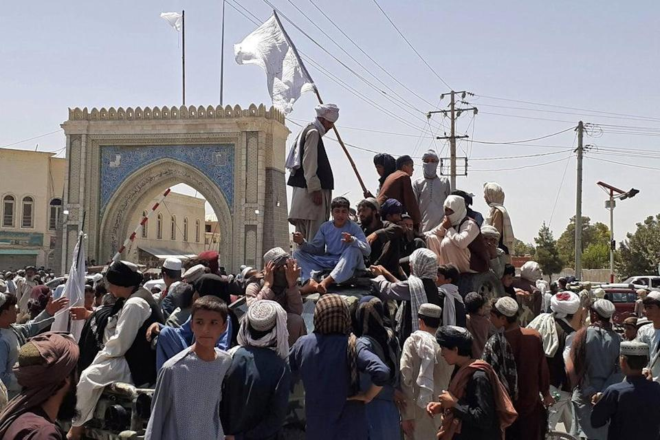 File: Taliban fighters stand on a vehicle along the roadside in Kandahar on 13 August 2021 (AFP via Getty Images)