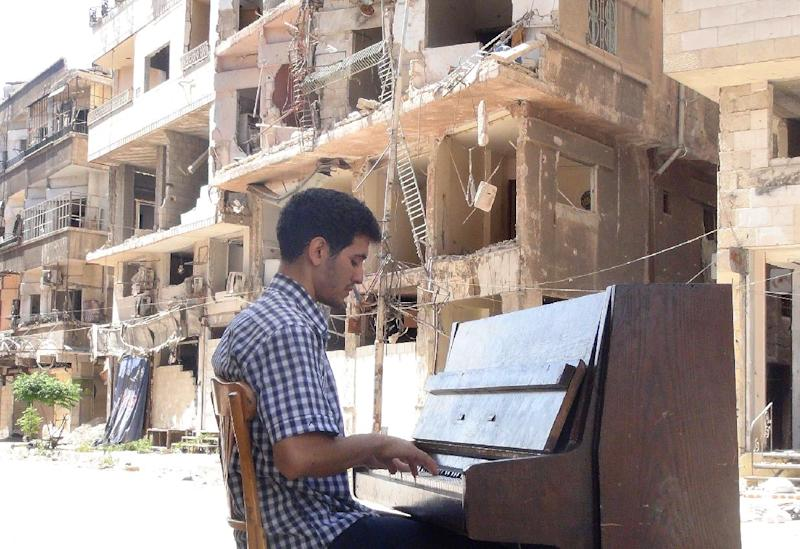 Ayham al-Ahmed, a resident of Damascus' Yarmuk Palestinian refugee camp, plays the piano in the middle of the street near destroyed buildings, on June 26, 2014 (AFP Photo/Rami Al-Sayed)