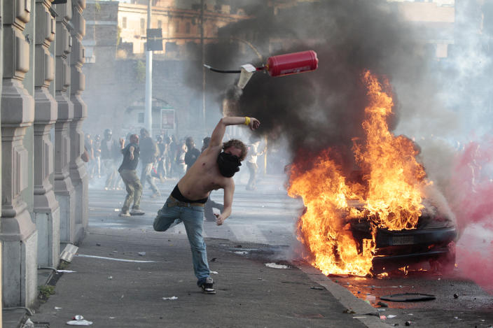 A protestor hurls a canister towards police next to a burning car during clashes in Rome, Saturday, Oct. 15, 2011. Protesters in Rome smashed shop windows and torched cars as violence broke out during a demonstration in the Italian capital, part of worldwide protests against corporate greed and austerity measures, entitled Occupy Wall Street.