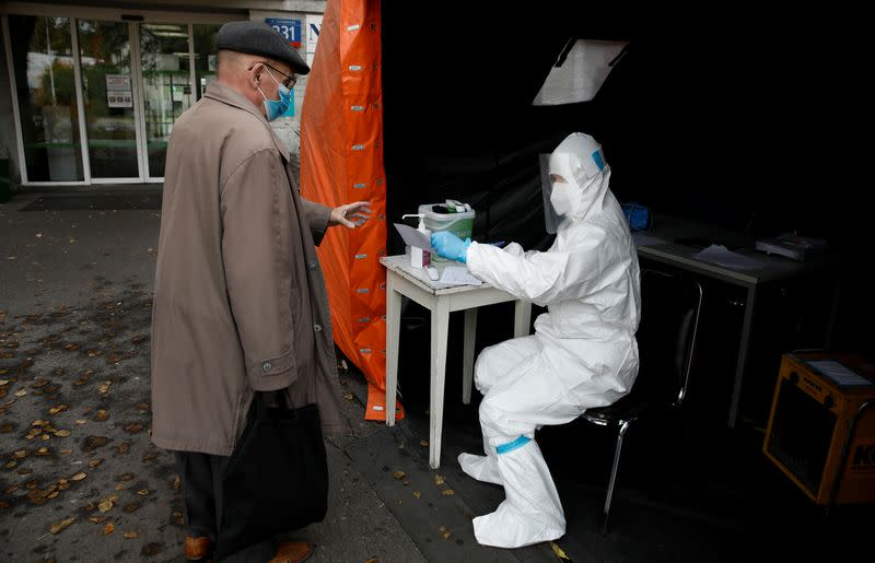 FILE PHOTO: A health worker in protective suit gives a document to man in Warsaw