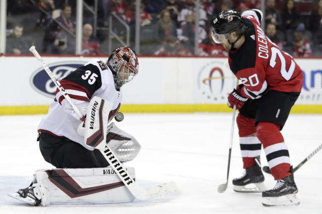 A shot by New Jersey Devils center Blake Coleman (20) is blocked by Arizona Coyotes goaltender Darcy Kuemper (35) during the second period of an NHL hockey game, Saturday, March 23, 2019, in Newark, N.J. (AP Photo/Julio Cortez)