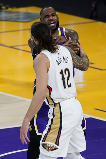Los Angeles Lakers forward LeBron James, top, and New Orleans Pelicans center Steven Adams (12) air their differences during the second quarter of an NBA basketball game Friday, Jan. 15, 2021, in Los Angeles. (AP Photo/Ashley Landis)