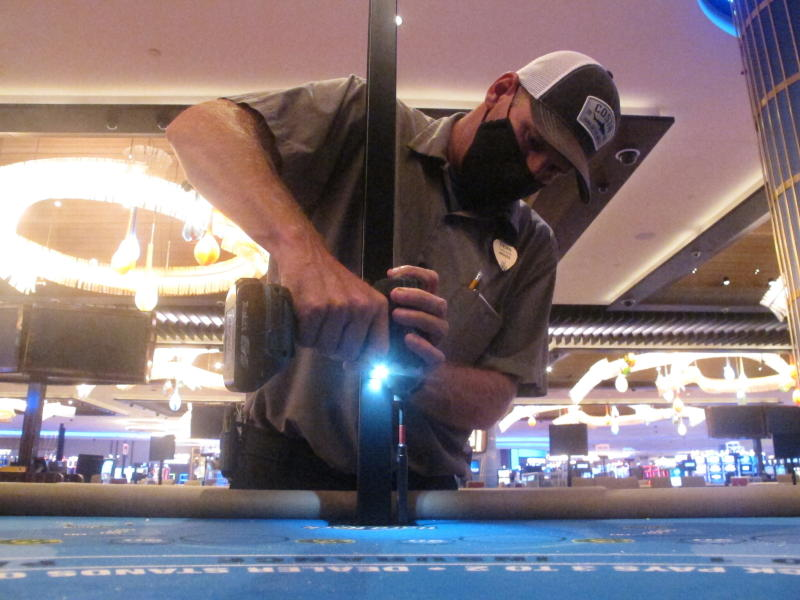In this June 24, 2020 photo, Dean Loveland, a worker at the Hard Rock casino in Atlantic City N.J., installs plexiglass barriers between player positions at a card table at the casino a week before it was to reopen amid the coronavirus outbreak. Smoking, drinking and eating will all be prohibited when Atlantic City's casinos reopen after being shut for three months due to the coronavirus outbreak under rules imposed by New Jersey Gov. Phil Murphy on June 29, 2020. (AP Photo/Wayne Parry)