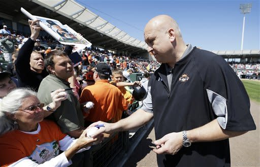 Former Baltimore Orioles shortstop Cal Ripken Jr. signs autographs before a spring training baseball game between the Orioles and the Toronto Blue Jays, Thursday, March 7, 2013, in Sarasota, Fla. (AP Photo/Charlie Neibergall)