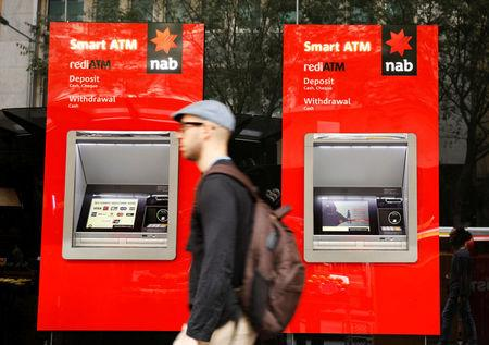A man walks past ATM machines at a National Australia Bank branch in Sydney, Australia