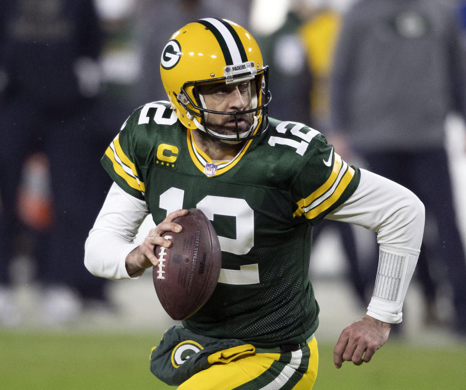 """FILE - In this Jan. 16, 2021, file photo, Green Bay Packers quarterback Aaron Rodgers (12) runs during an NFL divisional playoff football game against the Los Angeles Rams in Green Bay, Wis. Packers general manager Brian Gutekunst says the team remains committed to Rodgers """"for the foreseeable future"""" one year after trading up in the first round to draft the three-time MVP's potential successor. (AP Photo/Jeffrey Phelps, File)"""
