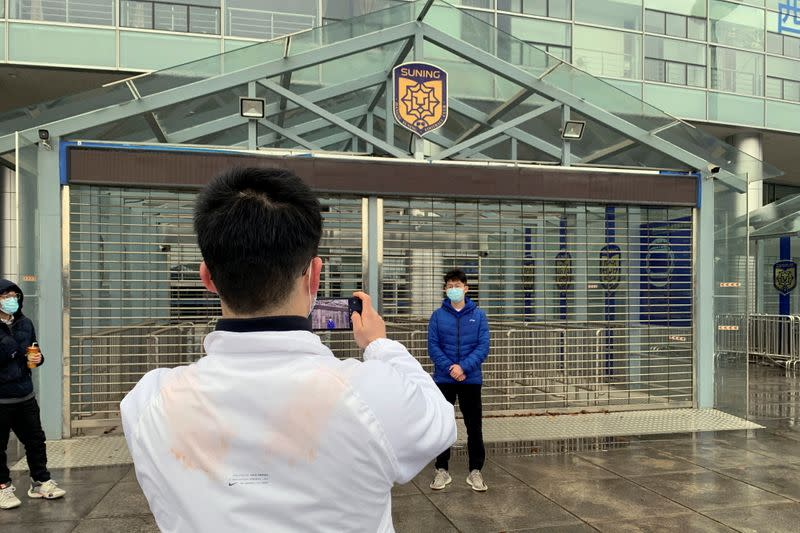 Fan poses for pictures outside the stadium of Chinese soccer club Jiangsu FC in Nanjing