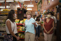 Sen. Tina Smith, center, D-Minn., receives a tour of El Burrito Mercado by her Latinx community engagement organizer, Ariana Bergeson, left, during a walking tour of Cesar Chavez Street businesses in St. Paul, Minn., Tuesday afternoon, Aug. 11, 2020. With them is state Sen. Sandy Pappas, right. (Jeff Wheeler/Star Tribune via AP)