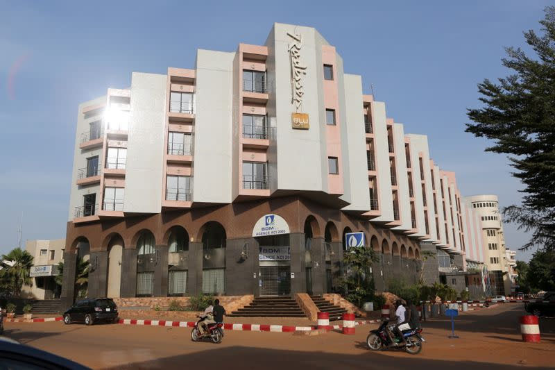 FILE PHOTO: People drive motorcycles past the Radisson Blu hotel in Bamako