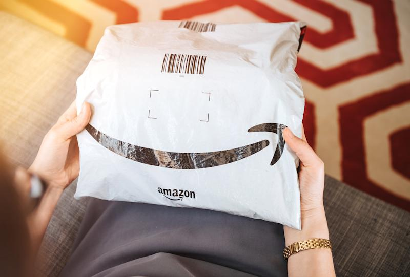 Paris, France - Aug 1, 2019: Overhead view of elegant woman on living room couch holding fresh Amazon Prime plastic package parcel with iconic logotype smile
