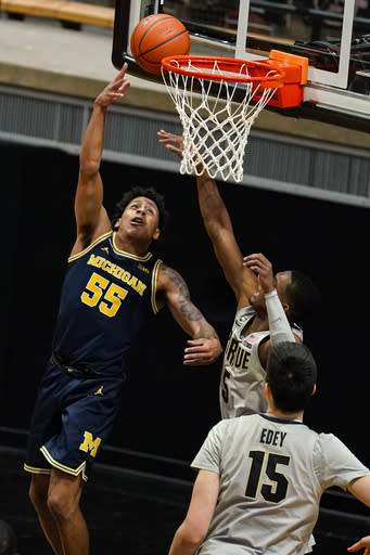 Michigan guard Eli Brooks (55) shoots in front of Purdue guard Brandon Newman (5) during the second half of an NCAA college basketball game in West Lafayette, Ind., Friday, Jan. 22, 2021. (AP Photo/Michael Conroy)