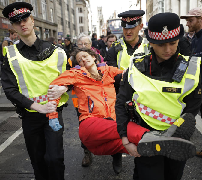 Police remove an Extinction Rebellion climate change protester who blocked a road outside the Goldman Sachs office in the City of London, Thursday, April 25, 2019. The non-violent protest group, Extinction Rebellion, is seeking negotiations with the government on its demand to make slowing climate change a top priority. (AP Photo/Matt Dunham)