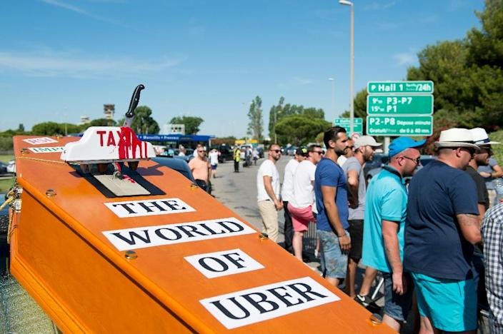 A mock coffin is displayed by striking taxi drivers as they block access to the Marignane airport near Marseille, southern France, on June 26, 2015 (AFP Photo/Bertrand Langlois)