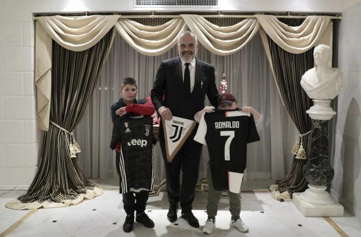 Albanian Prime Minister Edi Rama, center, poses with Aurel Lala and Alesio Cakoni, in Rome on Friday, Dec. 6, 2019. The two Albanian children were injured when they escaped their collapsing flat jolted from the Nov. 26 6.4-magnitude earthquake, that killed 51 persons and injured more than 3,000 others. They lost each two family members but their dream came true when Rama took them to Rome, Italy to meet with their sport idols Ronaldo and Buffon. (Albanian Prime Minister Office via AP)