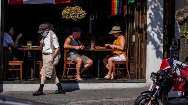 A group of people eat in a restaurant in Vancouver on July 1. Beginning next month, proof of vaccination will be required for patio and indoor dining. (Ben Nelms/CBC - image credit)