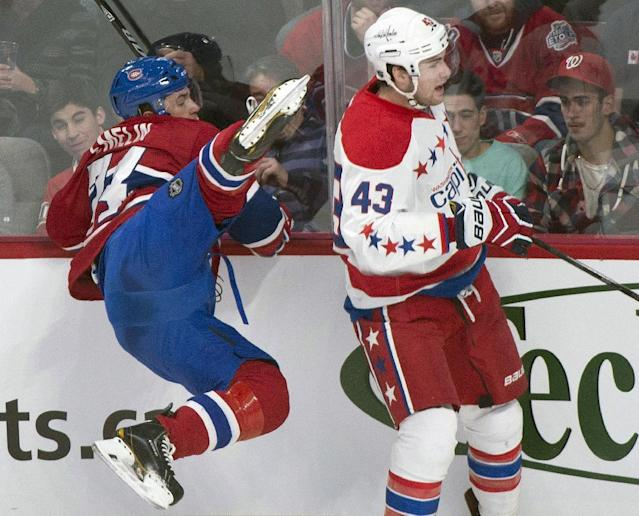 Montreal Canadiens' Alexei Emelin, left, is upended by Washington Capitals' Tom Wilson during the first period of an NHL hockey game in Montreal, Saturday, Jan. 25, 2014. (AP Photo/The Canadian Press, Graham Hughes)