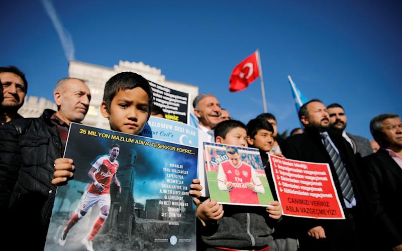 Ethnic Uighur boys hold placards with the pictures of English soccer club Arsenal's midfielder Mesut Ozil during a protest against China in Istanbul, Turkey December 14, 2019. The placard reads: