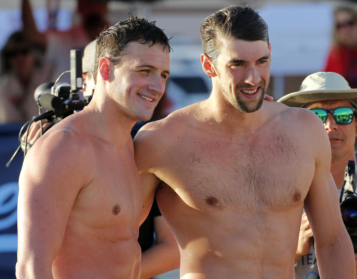 Michael Phelps, right, and Ryan Lochte pose for a photo after competing in the 100-meter butterfly final during the Arena Grand Prix swim meet, Thursday, April 24, 2014, in Mesa, Ariz. It is Phelps' first competitive event after a nearly two-year retirement. Lochte finished first and Phelps finished second. (AP Photo/Matt York)