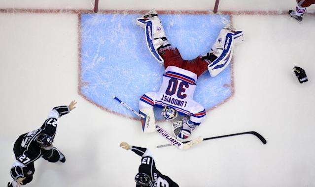 Los Angeles Kings defenseman Alec Martinez, lower left, celebrates with Kyle Clifford, lower right, after scoring the winning goal past New York Rangers goalie Henrik Lundqvist, top, of Sweden, during the second overtime period in Game 5 of an NHL hockey Stanley Cup finals, Friday, June 13, 2014, in Los Angeles. (AP Photo/Mark J. Terrill)