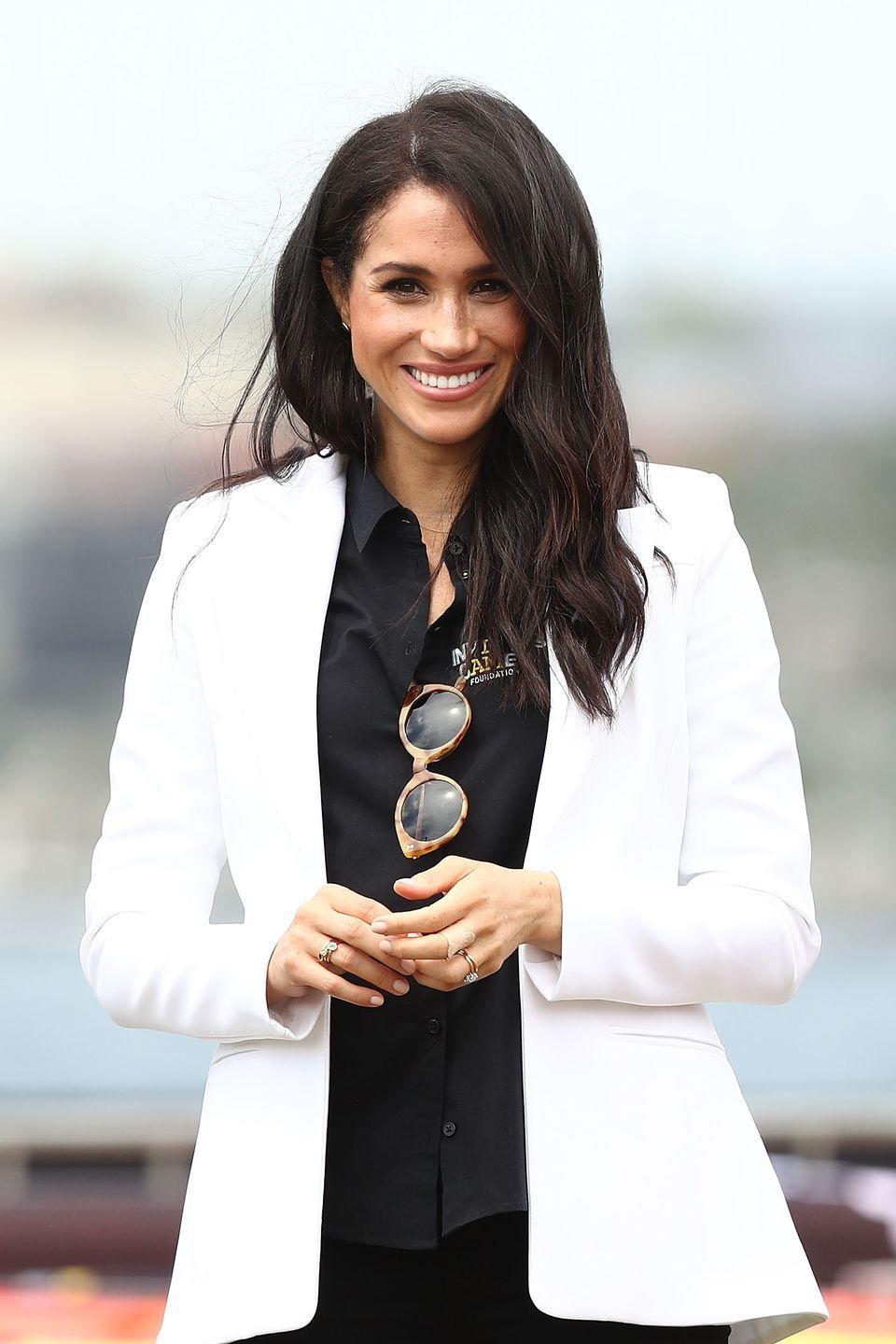 <p>On a 2018 trip to New Zealand, the Duchess of Sussex wore a black ensemble which she finished with a crisp white blazer, an unexpected but no less fashionable choice. </p>