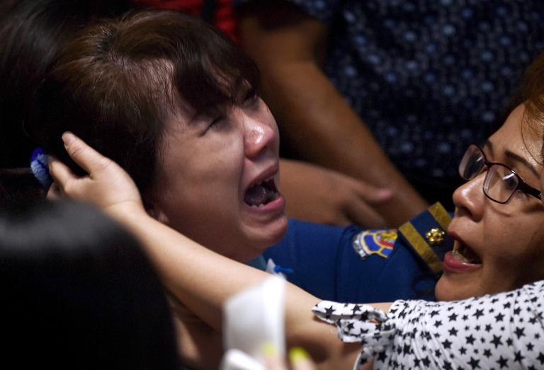 Family members of passengers onboard AirAsia flight QZ8501 react after watching television reports showing an body floating in the Java Sea, while waiting at a crisis-centre set up at Juanda International Airport in Surabaya, on December 30, 2014
