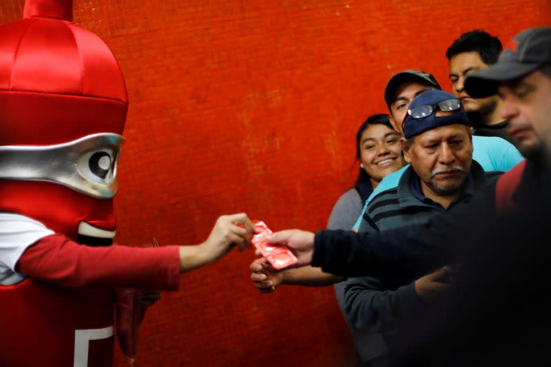 A man wearing a condom costume gives out free condoms inside the metro on International Condoms Day, celebrated a day before Valentine Day, in Mexico City